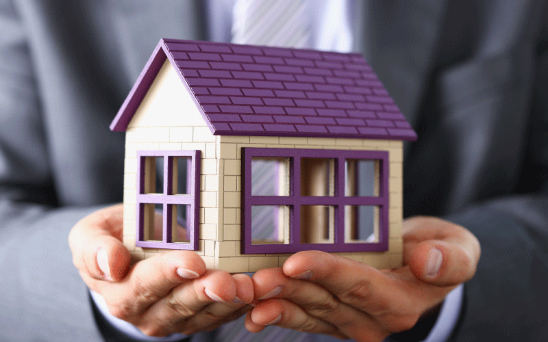a person holding a house - mortgage protection insurance