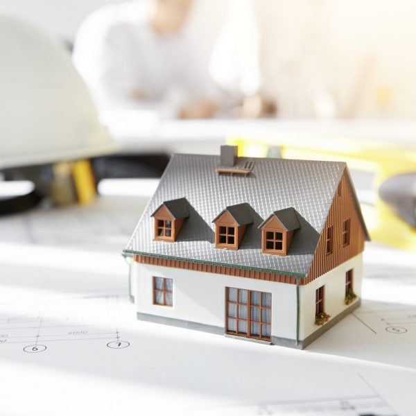 Design and architecture. Caucasian engineer working on drawings of new housing project, sitting in office with blueprint, ruler, divider compass and tape measure. Selective focus on scale model house